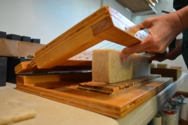 "Cutting the soaps. The cutting ""board"" is made by DuBois, and uses piano wires."